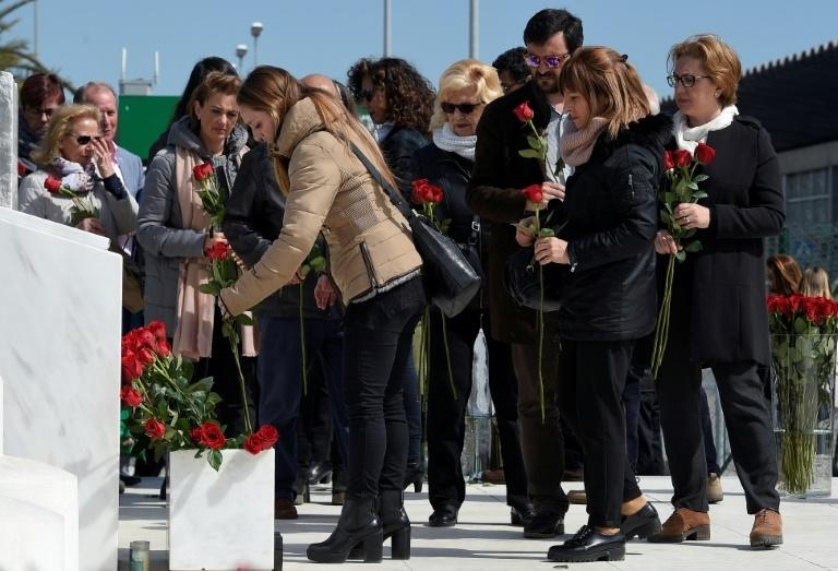 Relatives of the victims of the Germanwings crash display flowers in front of the commemorative plaque set for the victims of the Germanwings plane which crashed into the French Alps and claimed 150 lives, at Barcelona's airport, in El Prat de Llobregat on March 23, 2017