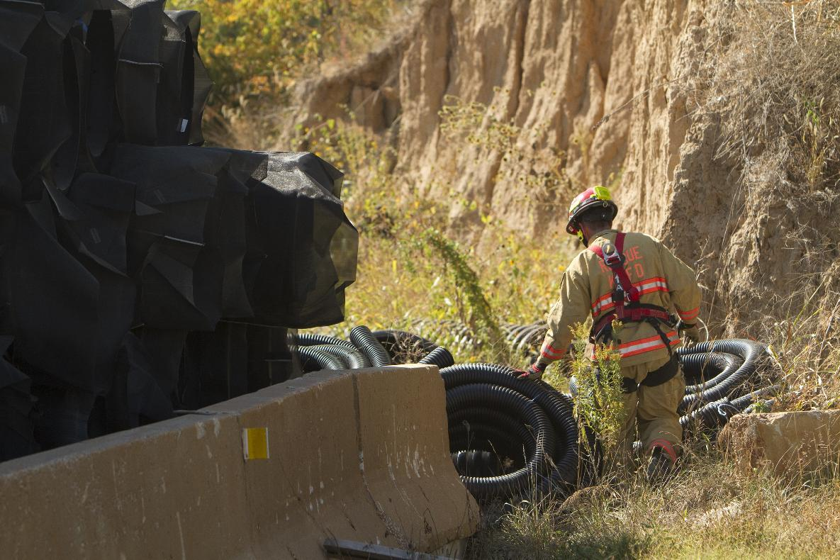A firefighter searches the area after rappelling down a steep embankment for missing 10-month-old Lisa Irwin in Kansas City, Mo. on Tuesday, Oct. 4, 2011. Lisa Irwin's mother reported last seeing the baby when she put her into her crib around 10:30 p.m. Monday. The father called police around 4 a.m. Tuesday when he returned home from his job at an electrical company and couldn't find the baby. (AP Photo/The Kansas City Star, Todd Feeback)