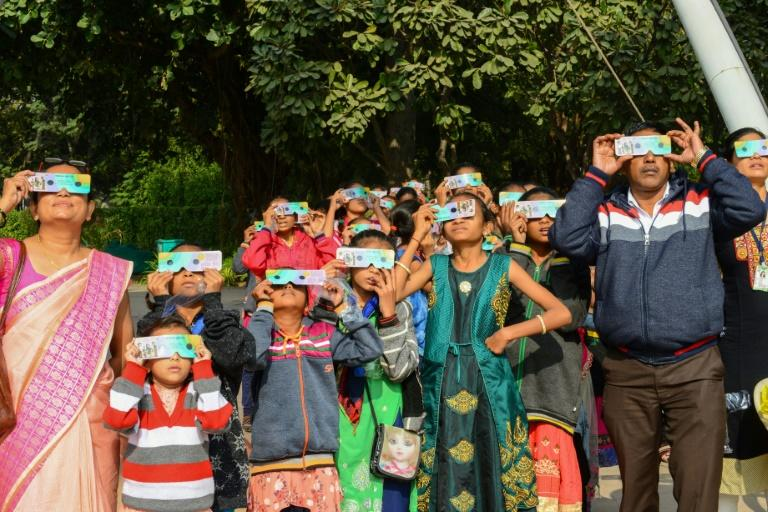 """Students and teachers use solar filter glasses to look at the """"ring of fire"""" solar eclipse at Gujarat Science City on the outskirts of Ahmedabad, India (AFP Photo/SAM PANTHAKY)"""