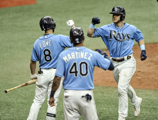 Tampa Bay Rays' Brandon Lowe (8) and Jose Martinez (40) congratulate Michael Brosseau, right, after his two-run home run off New York Yankees starter James Paxton during the seventh inning of a baseball game Sunday, Aug. 9, 2020, in St. Petersburg, Fla. (AP Photo/Steve Nesius)