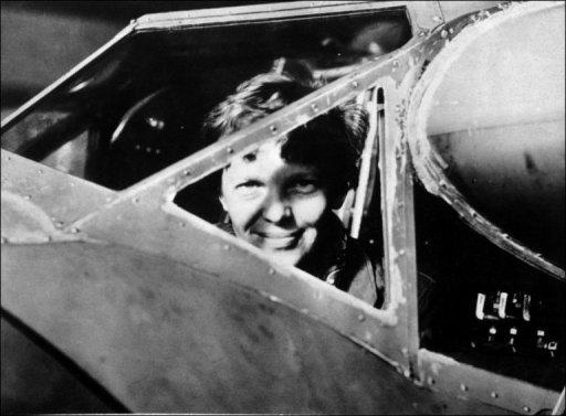 American aviator Amelia Earhart looks through the cockpit window of her plane in this undated photo taken in the 1930s. Amelia Earhart was the first woman to fly across the Atlantic. In 1935 she flew solo from Hawaii to California. In 1937, with Fred Noonan, she set out to fly around the world, but their plane was lost over the Pacific