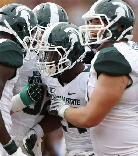 Michigan State's Le'Veon Bell, center, celebrates his second-quarter touchdown with teammates, including Travis Jackson, right, and Tony Lippett, left, during an NCAA college football game against Central Michigan, Saturday, Sept. 8, 2012, in Mount Pleasant, Mich. (AP Photo/Al Goldis)