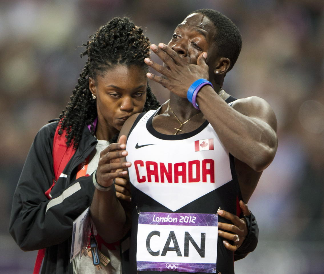 Canada's Justyn Warner is comforted after the Canadian relay team had their third place finish disqualified in the men's 4x100 metre final at the 2012 Summer Olympics in London, Saturday, August 11, 2012.THE CANADIAN PRESS/Ryan Remiorz