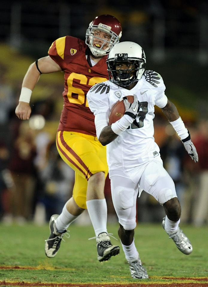 LOS ANGELES, CA - OCTOBER 30:  Cliff Harris #13 of the Oregon Ducks runs past Chris Pousson #62 of the USC Trojans during the second quarter at Los Angeles Memorial Coliseum on October 30, 2010 in Los Angeles, California.  (Photo by Harry How/Getty Images)