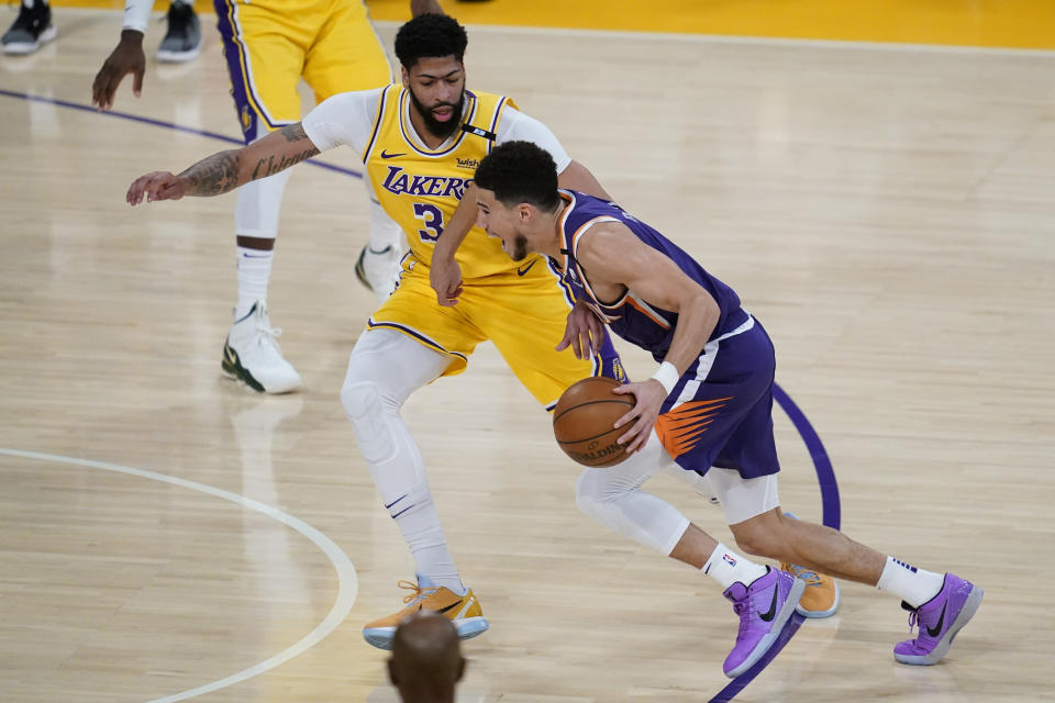 Los Angeles Lakers forward Anthony Davis (3) defends against Phoenix Suns guard Devin Booker (1) during the first quarter of Game 6 of an NBA basketball first-round playoff series Thursday, Jun 3, 2021, in Los Angeles. (AP Photo/Ashley Landis)