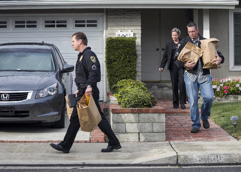 Police investigators take away evidence from the home of the mother of fugitive suspect former Los Angeles police officer Christopher Dorner, in La Palma, Calif., on Friday, Feb. 8, 2013. Police agencies have launched a massive manhunt for Dorner, who is suspected of killing a couple over the weekend and opening fire on four officers early Thursday, killing one and critically wounding another, authorities said. (AP Photo/Damian Dovarganes)