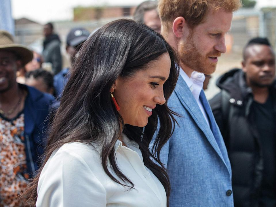 Prince Harry and Meghan leave the Youth Employment Services Hub in Tembisa township, Johannesburg (AFP via Getty Images)
