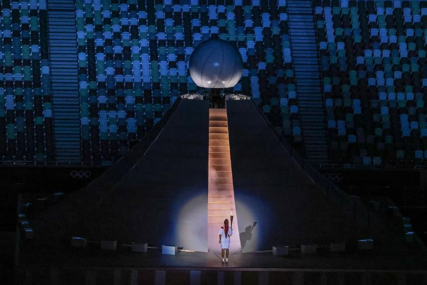 Tokyo, Japan, Friday, July 23, 2021 - Naomi Osaka prepares to scale stairs to light the Olympic flame at the Tokyo 2020 Olympics Opening Ceremony at Olympic Stadium. (Robert Gauthier/Los Angeles Times)
