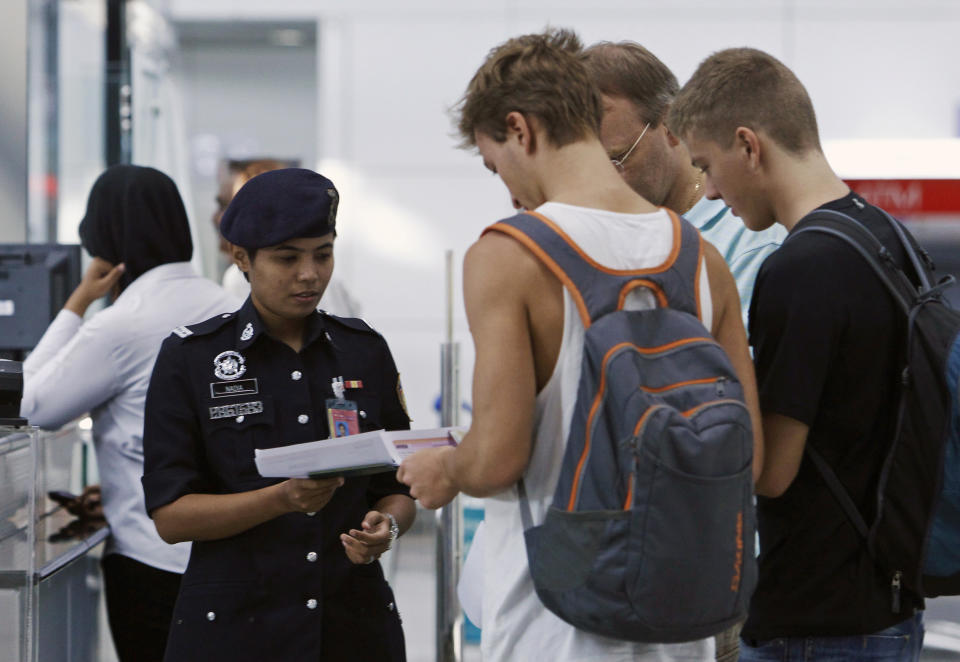 A customs officer checks the travel documents and passports of passengers at Kuala Lumpur International Airport in Sepang March 9, 2014. Malaysia Airlines flight MH370 carrying 227 passengers and 12 crew was presumed to have crashed off the Vietnamese coast on Saturday, and European officials said two people on board were using false identities. Malaysia Airlines said on Sunday it now feared the worst for its missing plane more than a day after it went missing, and was working with a U.S. company that specializes in disaster recovery.  REUTERS/Edgar Su (MALAYSIA - Tags: DISASTER TRANSPORT TRAVEL)