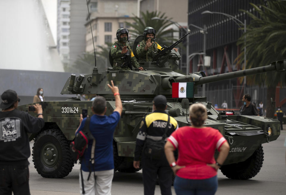 Crew members of a Mexican army armored vehicle wave to spectators during the annual Independence Day military parade on Mexico City's Juarez Avenue, Wednesday, Sept. 16, 2020. Mexico celebrates the anniversary of its independence uprising of 1810. (AP Photo/Fernando Llano)