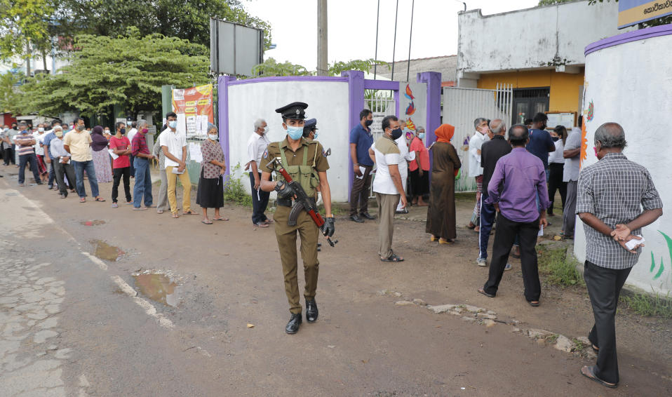 Sri Lankans stand in a queue as a police officer stands guard outside a polling station in Colombo, Sri Lanka, Wednesday, Aug. 5, 2020. Sri Lankans started voting Wednesday to elect a new Parliament that is expected to give strong support to the powerful and popular Rajapaksa brothers. (AP Photo/Eranga Jayawardena)
