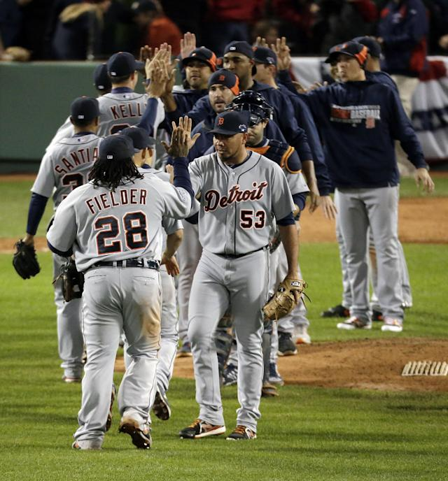 Detroit Tigers' Prince Fielder (28) congratulates relief pitcher Joaquin Benoit (53) as teammates celebrate their 1-0 win against the Boston Red Sox in Game 1 of the American League baseball championship series Sunday, Oct. 13, 2013, in Boston. (AP Photo/Charlie Riedel)
