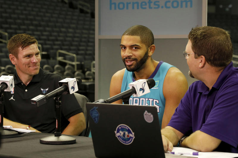 Charlotte Hornets' Nicolas Batum, of France, center, talks with radio personalities during the NBA basketball team's media day in Charlotte, N.C., Monday, Sept. 30, 2019. (AP Photo/Bob Leverone)