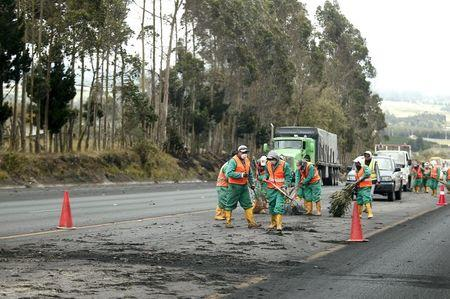 Workers sweep the road to remove ash spewed by the Cotopaxi volcano in Chasqui, Ecuador, August 14, 2015. REUTERS/Guillermo Granja