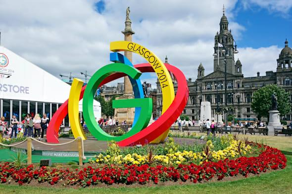 Glasgow 2014 XX Commonwealth Games brand logo in George Square Glasgow with Superstore left and Glasgow City Council building