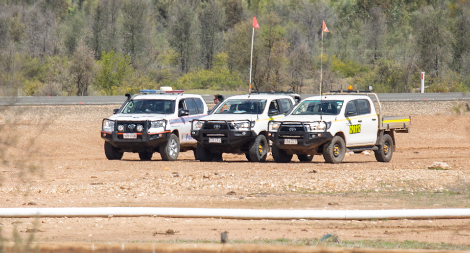 Police and mining vehicles in the distance.