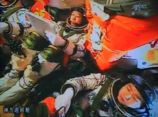 A photo of the giant screen at the Jiuquan space center shows three Chinese astronauts (from left) Liu Wang, Jing Haipeng and Liu Yang in the Shenzhou-9 spacecraft in the preparation for docking with the Tiangong-1 module on Monday. The three have entered an orbiting module for the first time, in a move broadcast live on China's state TV and a key step towards the nation's first space station