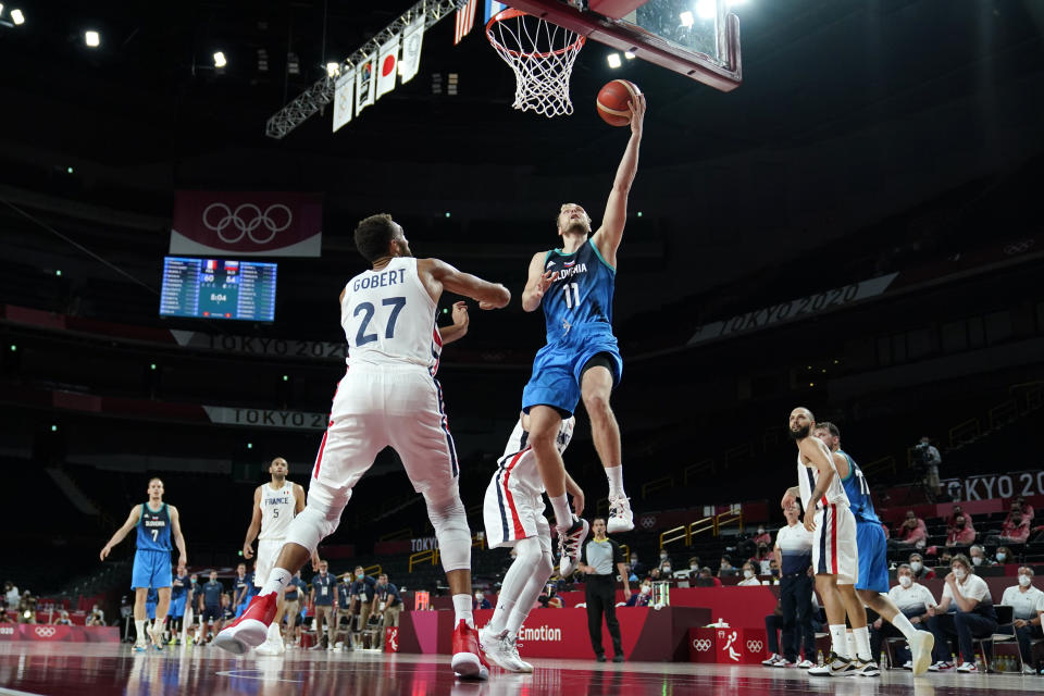 Slovenia's Jaka Blazic (11) drives to the basket over France's Rudy Gobert (27) during a men's basketball semifinal round game at the 2020 Summer Olympics, Thursday, Aug. 5, 2021, in Saitama, Japan. (AP Photo/Charlie Neibergall)
