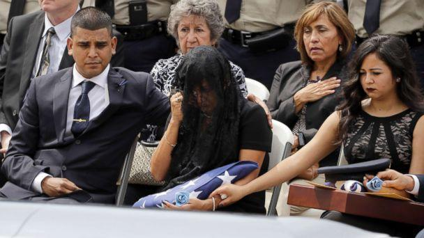PHOTO: Cheryl Perez, center, is comforted by her son, Maverick, left, and daughter, Sabrina, during a funeral service for her husband, Houston Police Sgt. Steve Perez, Sept. 13, 2017, in Houston. (David J. Phillip/AP)