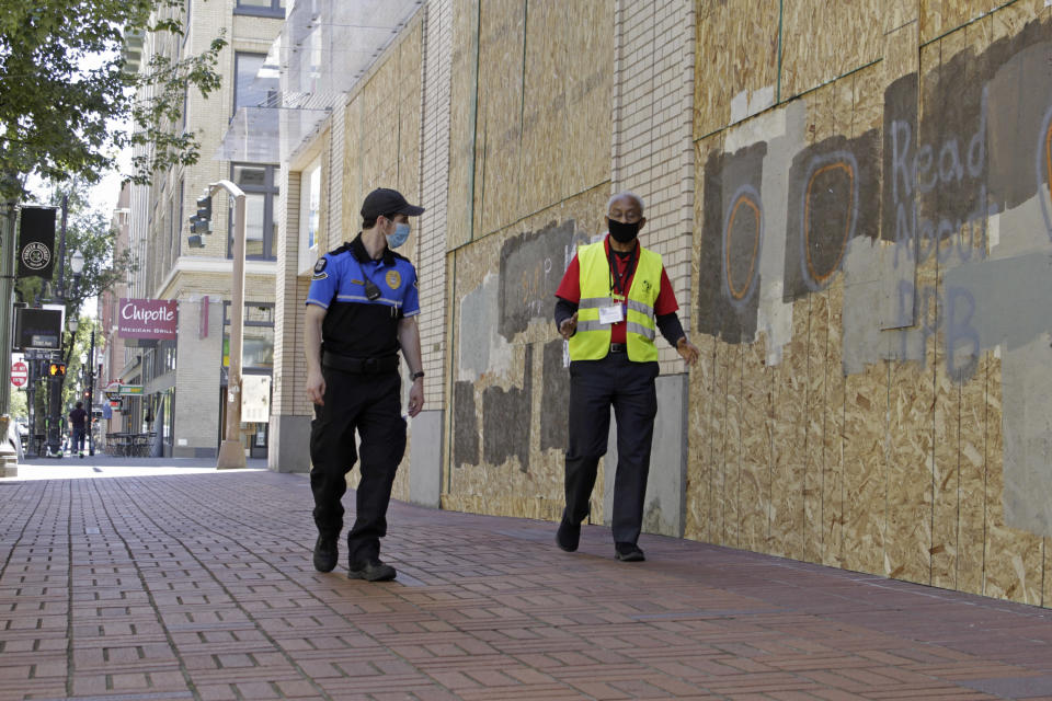 Two security officers walk in downtown Portland, Ore., Monday, July 13, 2020, alongside an entire block of shop windows that have been boarded up following nightly protests that have been going on for seven weeks. Violent clashes between protesters and police have divided the liberal city, paralyzed the downtown and attracted the attention of President Donald Trump, who sent federal law enforcement to the city to quell protests. (AP Photo/Gillian Flaccus)