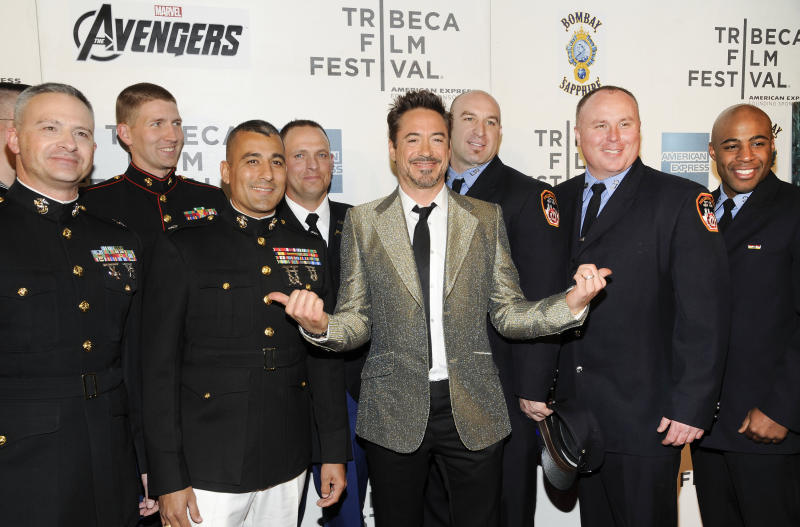 """Actor Robert Downey Jr., center, poses with members of the U.S. Military and New York Fire Department before the premiere of """"The Avengers"""" during the 2012 Tribeca Film Festival on Saturday, April 28, 2012 in New York. (AP Photo/Evan Agostini)"""