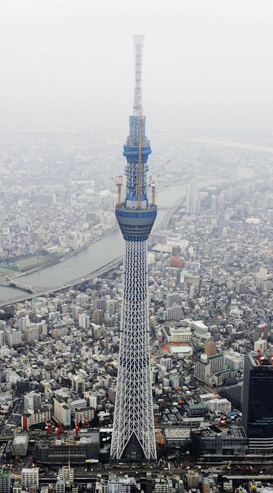 Tokyo Sky Tree, a new landmark tower which is still under construction in Tokyo, dwarfs other buildings Tuesday, March 1, 2011. The new broadcast tower reached the height of 1,971 feet (601 meters) Tuesday and became the world's tallest freestanding tower, outgrowing the 1,968 feet (600-meter) Canton Tower in China's southwestern city of Guanzhou, operator Tobu Tower Sky Tree Co. said. (AP Photo/Kyodo News) JAPAN OUT, MANDATORY CREDIT, FOR COMMERCIAL USE ONLY IN NORTH AMERICA