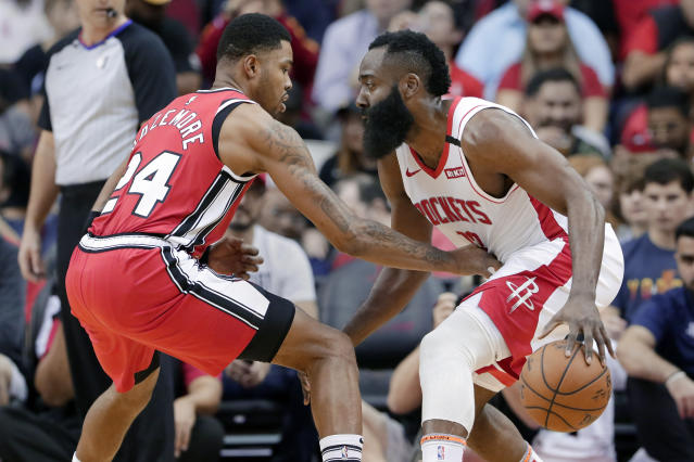 Houston Rockets guard James Harden, right, looks for a way around Portland Trail Blazers guard Kent Bazemore (24) during the first half of an NBA basketball game Wednesday, Jan. 15, 2020, in Houston. (AP Photo/Michael Wyke)
