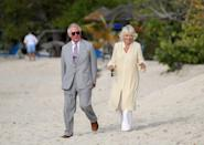 <p>Upon arriving in Grenada, Prince Charles and the Duchess of Cornwall took a stroll along a beach in St. George. Camilla wore a cream colored caftan with white embroidery, white wide leg pants, and sunglasses. </p>
