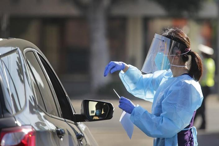 LOS ANGELES, CA - OCTOBER 03: Health worker Hannah Kwon explains to a individual in car, on how to use oral swabs at a drive-thru COVID-19 test site established by Councilman Herb Wesson in collaboration with Kheir Clinic at his district office on Saturday, Oct. 3, 2020 in Los Angeles, CA. (Irfan Khan / Los Angeles Times)