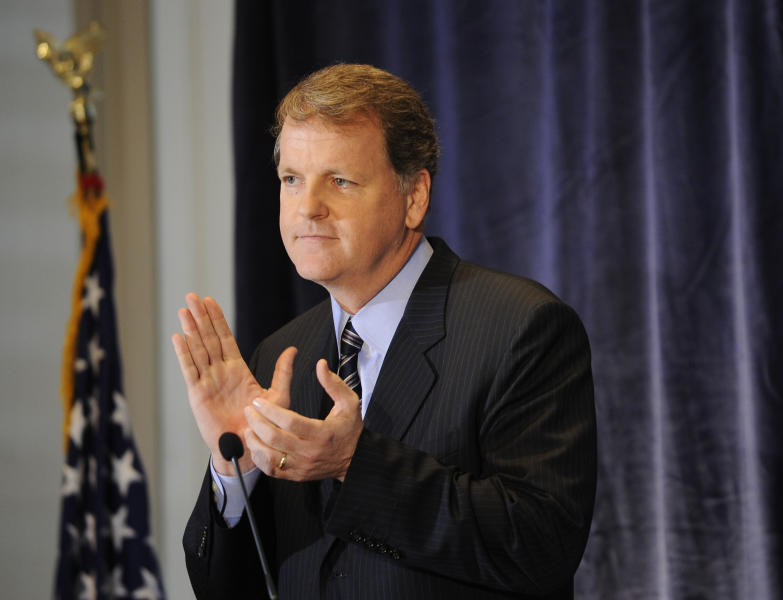 FILE - In this Jan. 15, 2012 file photo, US Airways CEO and Chairman Doug Parker applauds the crew of flight 1549 in New York. Since American's parent AMR Corp. filed for bankruptcy last November, Parker has been aggressively promoting a combination of the two airlines as the only way to save American. Parker has championed the idea on Wall Street, in the media and lined up support from the three labor unions at American. Investors have treated the possibility as a near inevitability, pushing shares of US Airways Group Inc. up 160 percent over the past seven months. (AP Photo/Stephen Chernin)