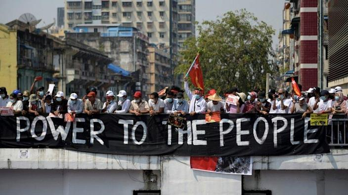 Demonstrators stand behind a banner as they protest against military coup in Yangon