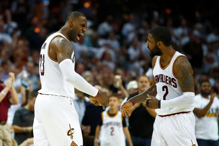 LeBron James (L) of the Cleveland Cavaliers celebrates a dunk with teammate Kyrie Irving, at Quicken Loans Arena in Cleveland, Ohio, on April 15, 2017
