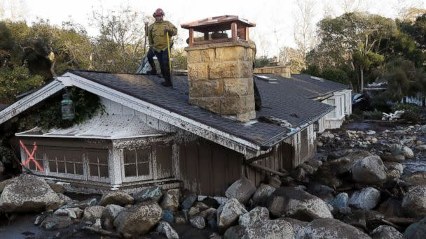 PHOTO: A firefighter stands on the roof of a house submerged in mud and rocks, Jan. 10, 2018, in Montecito, Calif. (Marcio Jose Sanchez/AP)