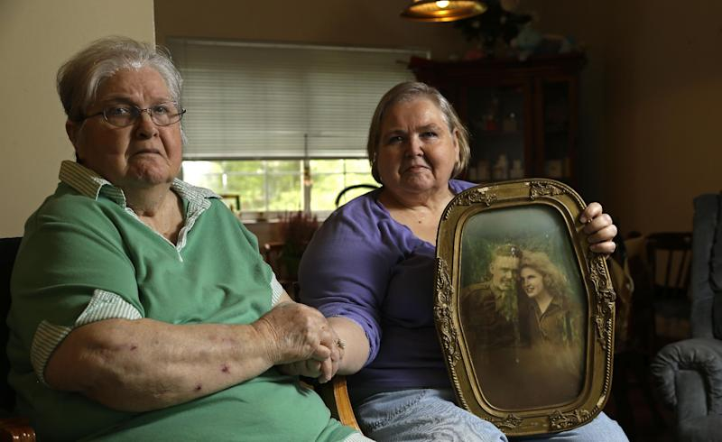 "In this photo taken Monday, July 1, 2013 in Chapel Hill, N.C., Shelia Reese, right, sits with her mother Chris Tench holding a portrait of Tench and her father Kenneth F. Reese, a soldier who is still Missing In Action from the Korean War. Tench, who was later remarried, has never known what happened to her husband. The Pentagon's effort to account for tens of thousands of Americans missing in action from foreign wars is so inept, mismanaged and wasteful that it risks descending from ""dysfunction to total failure,"" according to an internal study suppressed by military officials. (AP Photo/Gerry Broome)"