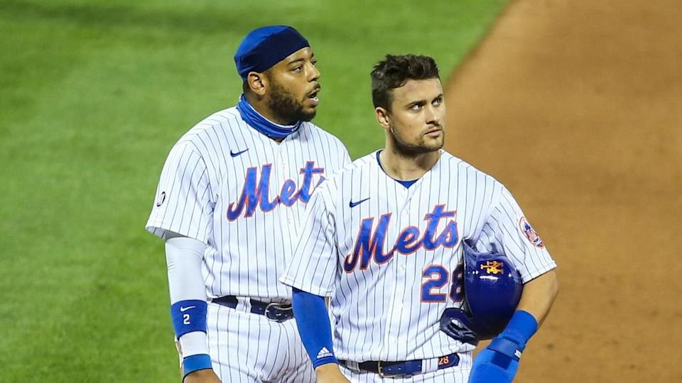 Dom Smith and J.D. Davis stand near first base with helmets off in home uniforms
