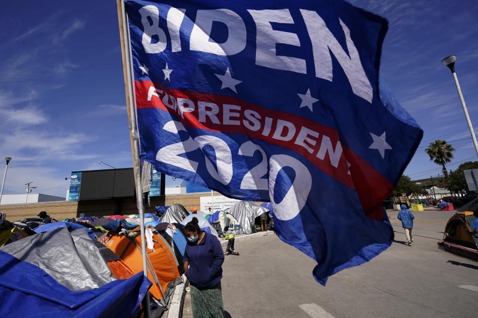 A woman passes a donated campaign flag for President Joe Biden at a makeshift camp of migrants at the border port of entry leading to the United States, Wednesday, March 17, 2021, in Tijuana, Mexico. The migrant camp shows how confusion has undercut the message from Biden that it's not the time to come to the United States. Badly misinformed, some 1,500 migrants who set up tents across the border from San Diego harbor false hope that Biden will open entry briefly and without notice. (AP Photo/Gregory Bull)