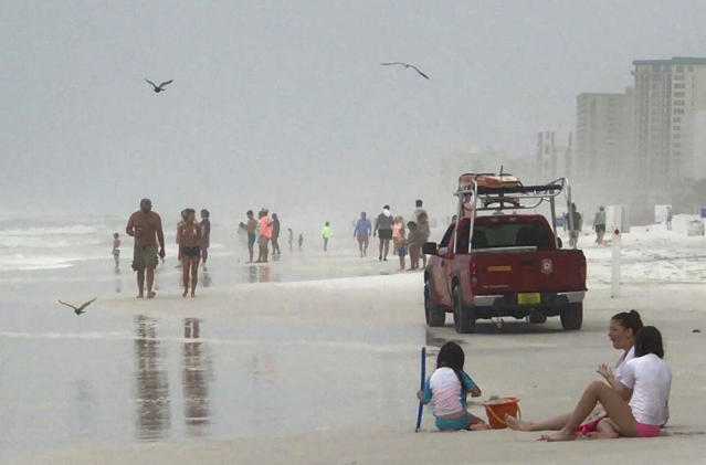 <p>A Destin Beach Safety truck drives past tourists as it patrols the shoreline along Destin, Fla., on June 21, 2017. (Photo: Annie Blanks/Northwest Florida Daily News via AP) </p>
