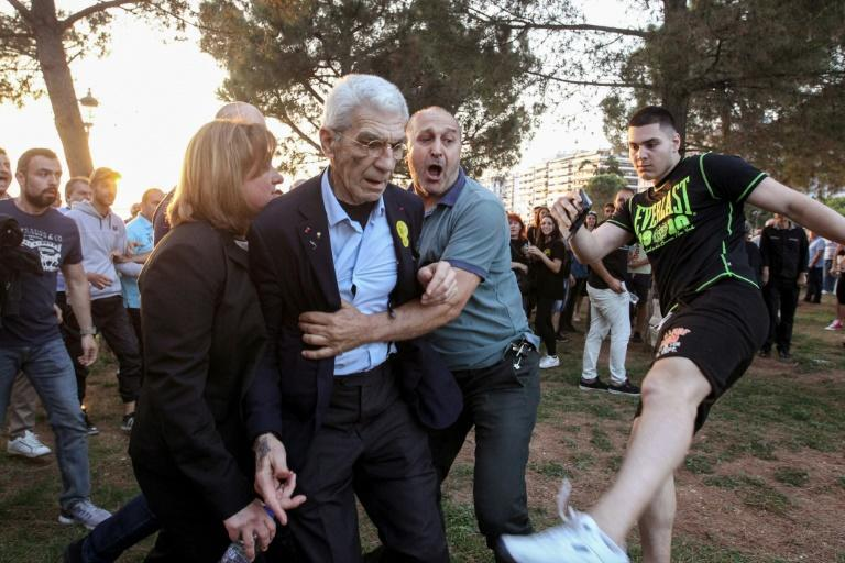 The mayor of Greece's second city, Thessaloniki, Yiannis Boutaris is helped  as he is assulted by suspected far-right supporters at a rally on Saturday
