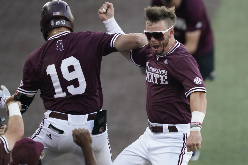 Mississippi State's Logan Tanner (19) celebrates with teammate Tanner Allen after hitting a second-inning three-run home run against Notre Dame during an NCAA college baseball super regional game, Monday, June 14, 2021, in Starkville, Miss. (AP Photo/Rogelio V. Solis)