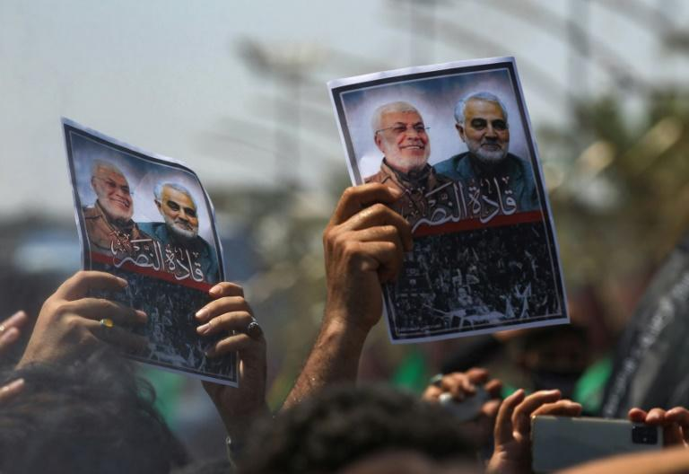 Mourners hold images of Iranian general Qasem Soleimani and senior Iraqi military commander Abu Mahdi al-Muhandis after they were killed in a US drone strike -- both men began their military careers in the Iran-Iraq war