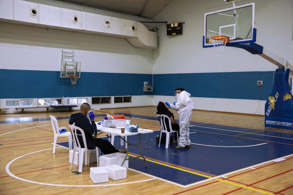A woman is tested for the coronavirus by a healthcare worker at a COVID-19 testing center, set up at a basketball court, in Ramat Gan, Israel, Tuesday, Oct 20, 2020. (AP Photo/Oded Balilty)