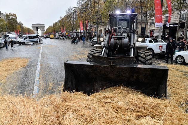 PARIS, FRANCE - NOVEMBER 27: A backhoe clears the straws covering the ground during a protest by farmers titled
