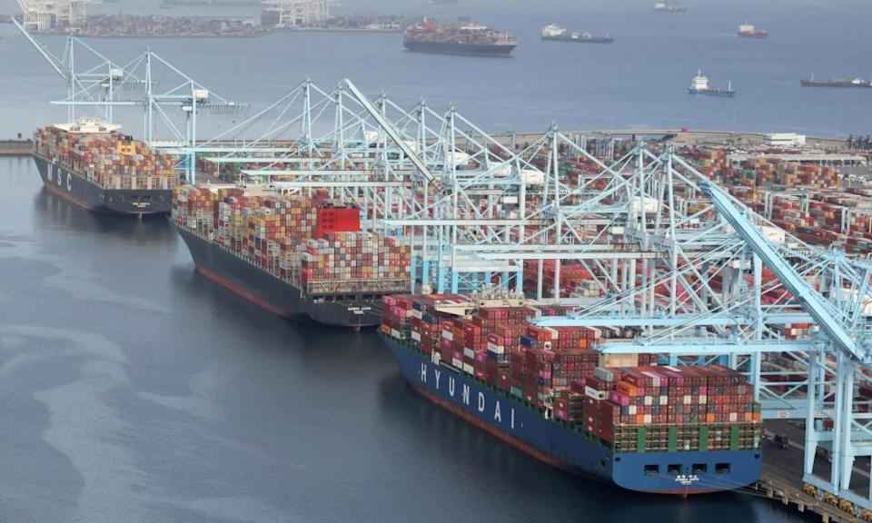 Shipping containers are unloaded from ships at a container terminal at the Long Beach-Los Angeles port complex in California