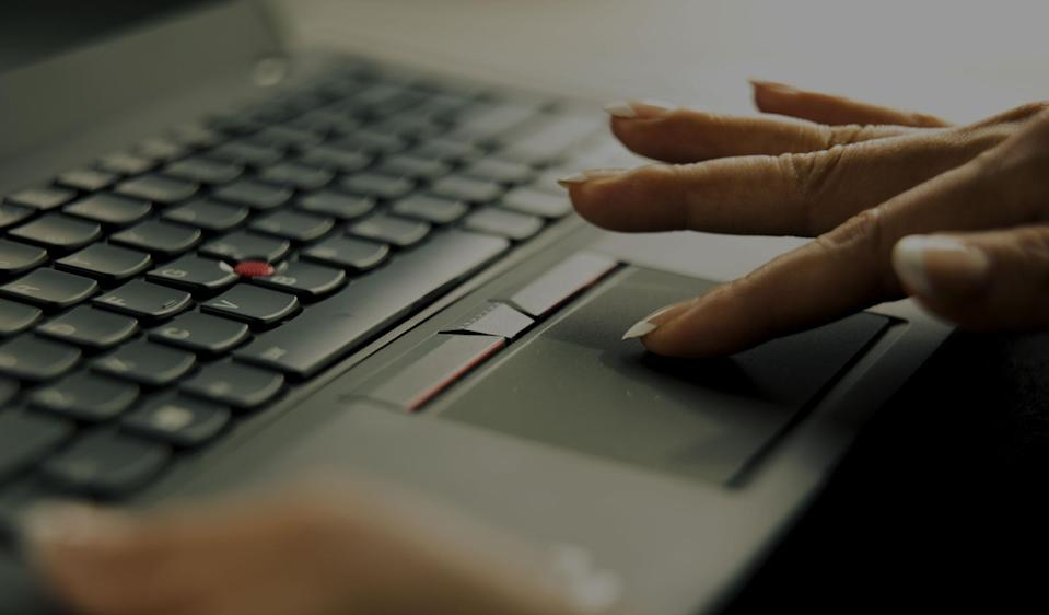 Finger touching a laptop touchpad.