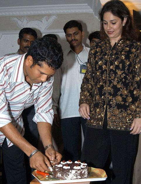 Indian cricketer Sachin Tendulkar (L) picks a piece of cake after he cut-it on the eve of his 31st birthday as his wife Anjali looks on in Bombay, 23 April 2004.  Tendulkar had a get-together with family and friends as he will be attending the wedding reception of his colleague Virender Sehwag who recently got married in Delhi.  AFP PHOTO