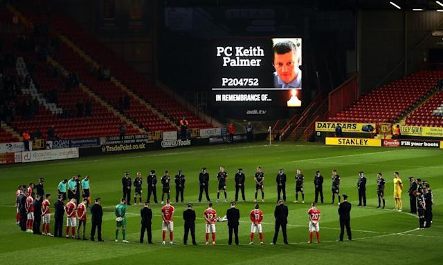 """<span class=""""element-image__caption"""">Players and policeman stand for a minute silence in tribute to PC Keith Palmer.</span> <span class=""""element-image__credit"""">Photograph: Bryn Lennon/Getty Images</span>"""