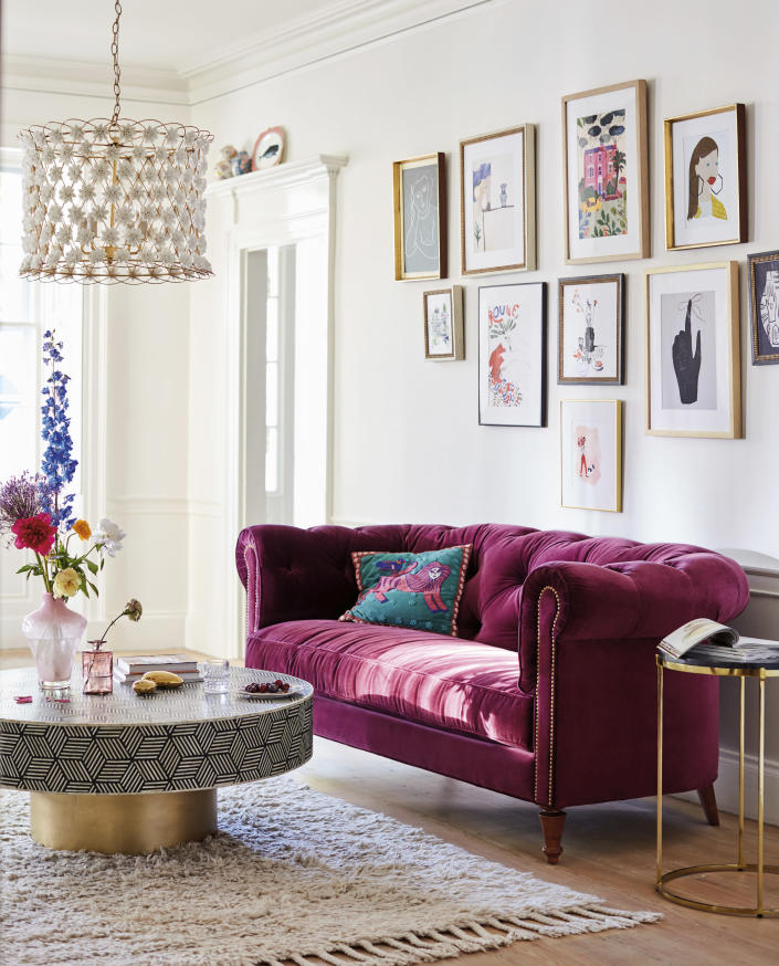 This undated photo provided by Anthropologie shows the Atelier chesterfield, a chic option with a rich mulberry hue, velvet upholstery and a deep comfy structure. Pair it with minimalist contemporary accessories to give it center stage, or play off its traditional aesthetic with lots of pattern and eclectic accompaniments. (Anthropologie via AP)