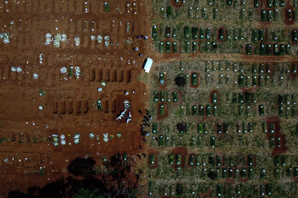 SAO PAULO, BRAZIL - MARCH 12: An aerial view of open graves at Vila Formosa Cemetery on March 12, 2021 in Sao Paulo, Brazil. Vila Formosa, the biggest graveyard in Latin America, has seen its activity grow in the last weeks due to the surge of deaths related to coronavirus. Burials and cremations in the capital of Sao Paulo grew 11% in the first week of March compared to February. The increase means that there is already a lack of raw material for the manufacture of coffins and recently, hearse jams and queues have been recorded at the cemetery. (Photo by Alexandre Schneider/Getty Images)