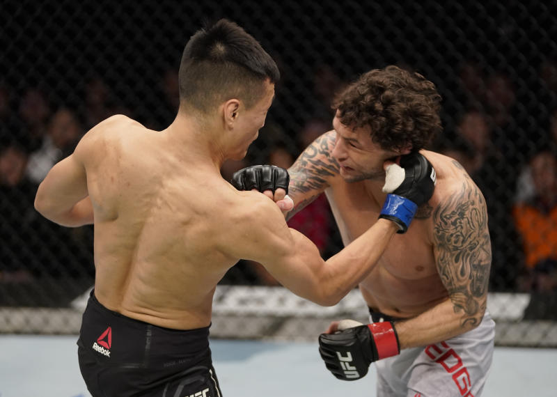 BUSAN, SOUTH KOREA - DECEMBER 21: (L-R) Chan Sung Jung of South Korea punches Frankie Edgar in their featherweight fight during the UFC Fight Night event at Sajik Arena 3 on December 21, 2019 in Busan, South Korea. (Photo by Jeff Bottari/Zuffa LLC via Getty Images)