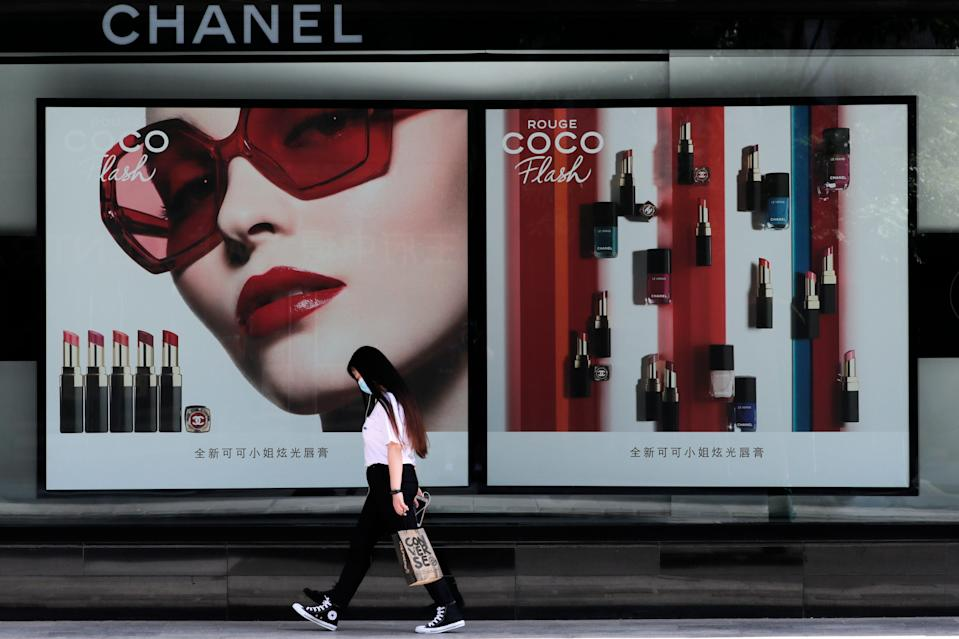 A woman wearing a face mask walks past a Chanel lipstick billboard in Beijing, May 28, 2020.